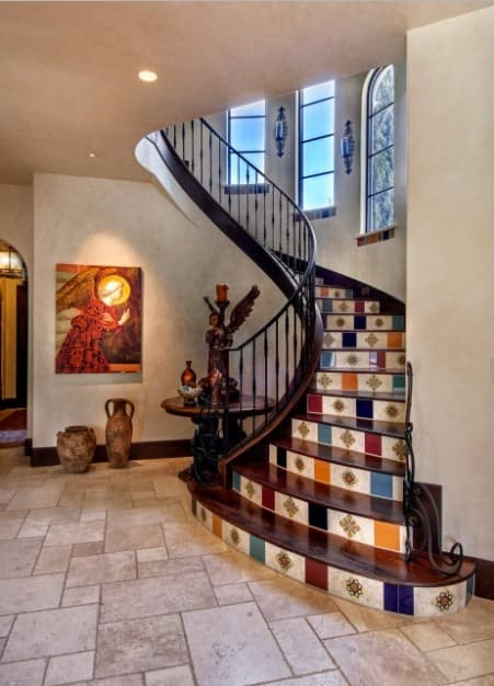 Mediterranean style staircase accented with multi-colored patterned risers and wooden treads framed with black steel railing. There's a round table beside it topped with an angel sculpture and decors.
