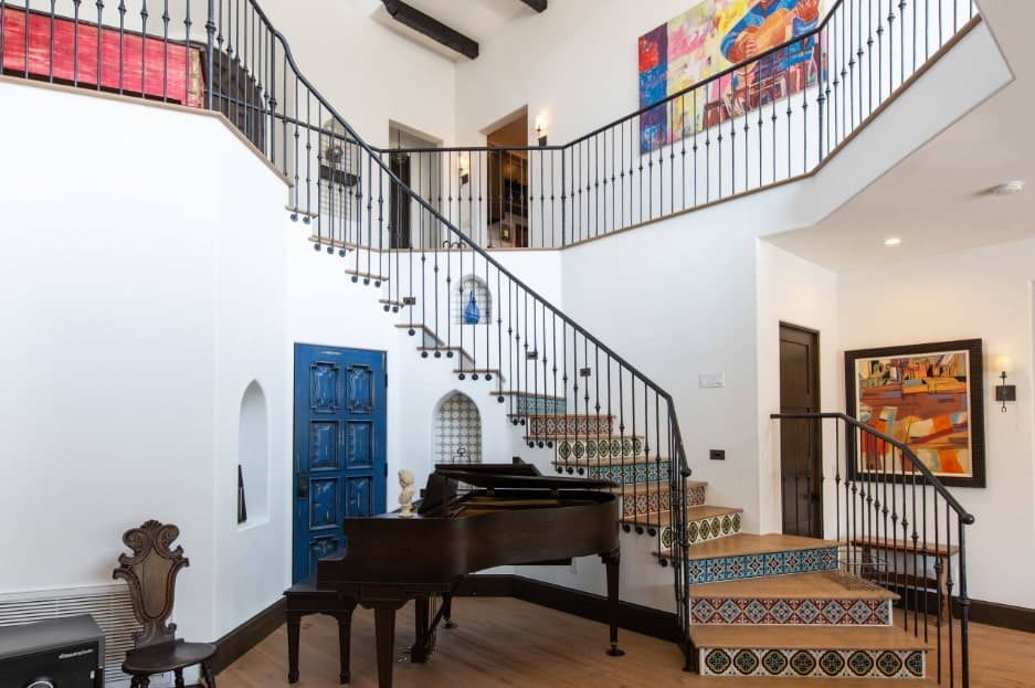 The Mediterranean foyer features a staircase styled with colorful patterned risers along with wrought iron railings and wooden treads. There's a baby grand piano at its front across a blue door.