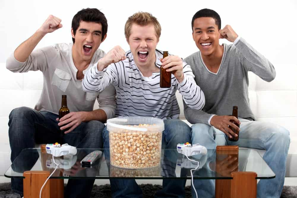A trio of young men reacting happily as they watch a game with a beer each in hand.