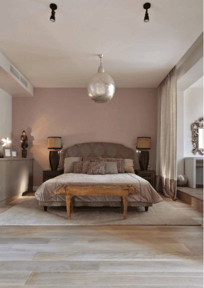 A huge silver pendant illuminates this master bedroom along with table lamps that sit on wooden nightstands. It has a pink patterned bed with a wooden bench on its end over light wood plank flooring.