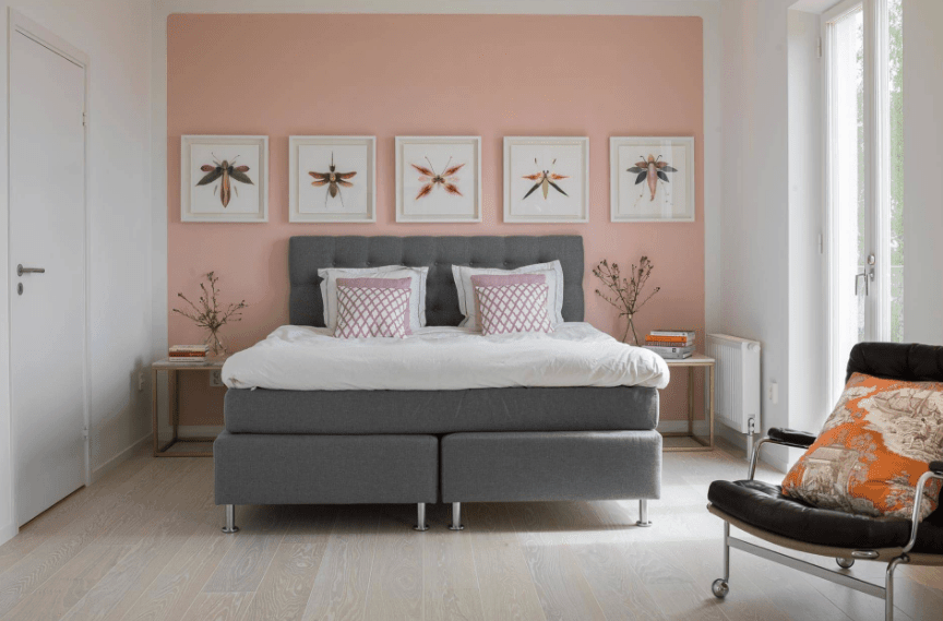 Primary bedroom with a pastel pink accent wall lined with white wall art pieces mounted above the gray bed. It is accompanied by wooden nightstands and a leather chair with orange printed pillow.