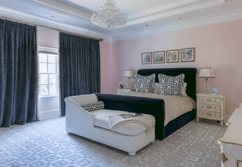 Elegant master bedroom showcases light pink walls contrasted by a navy blue bed and velvet deep blue curtains lined with tassels covering a white framed window.