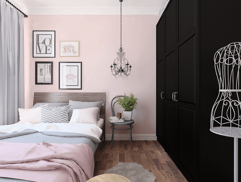 Scandinavian bedroom boasts a black full height wardrobe facing the wooden bed with gray and pink bedding. It is decorated with gallery frames and vintage chandelier along with a potted plant on a gray chair.