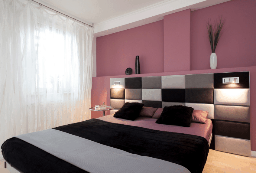 Pink master bedroom accented with a black bed that's framed with a custom paneled headboard. It has black and gray panels fitted with built-in lights.