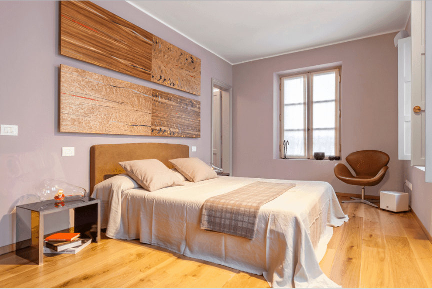 Primary bedroom with nude pink walls and multi-panel wood wall arts mounted above the bed. It has mirrored nightstands and a leather accent chair in the corner.