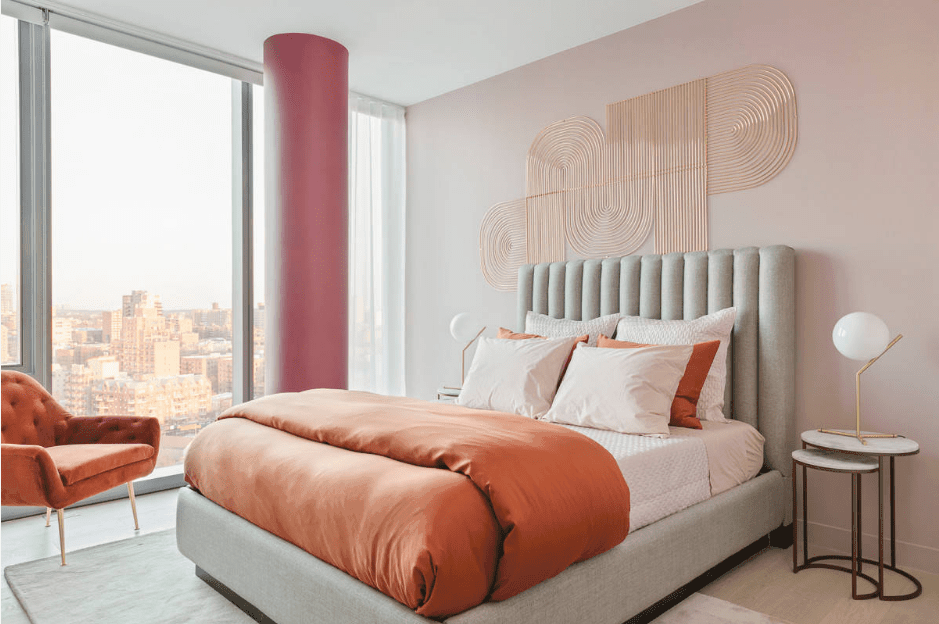 This master bedroom boasts a copper pink wall art and full height glazing overlooking an amazing city view.