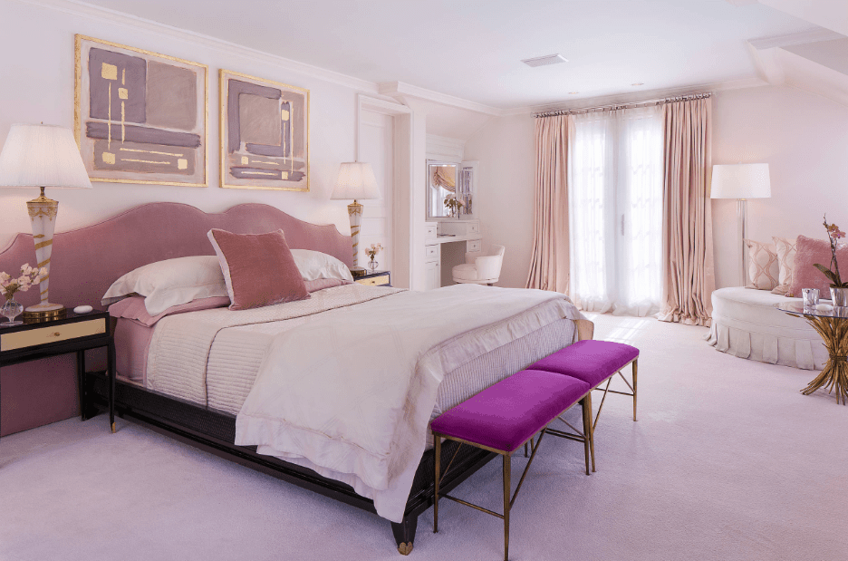 Magnificent master bedroom designed with a pair of gorgeous wall art pieces mounted above the upholstered bed. It has a cuddle chair lighted by a floor lamp and faces the white vanity area.