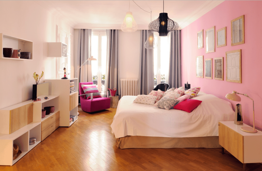 Primary bedroom designed with various styled pendant lights and gallery frames mounted on the pink wall.
