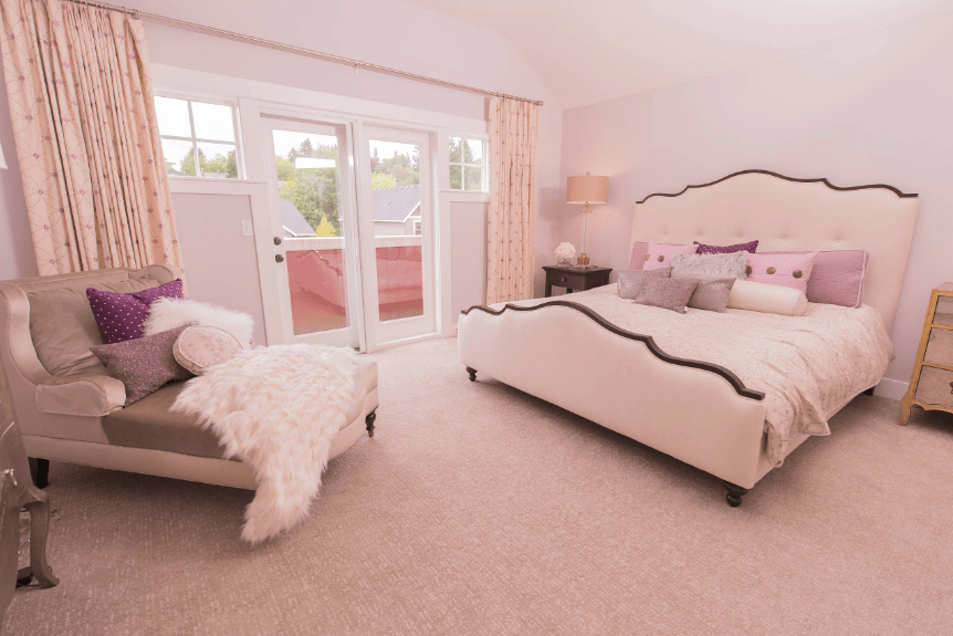 A gray chaise lounge accented with multi-colored pillows and a fur blanket faces the lovely white bed in this pink master bedroom.