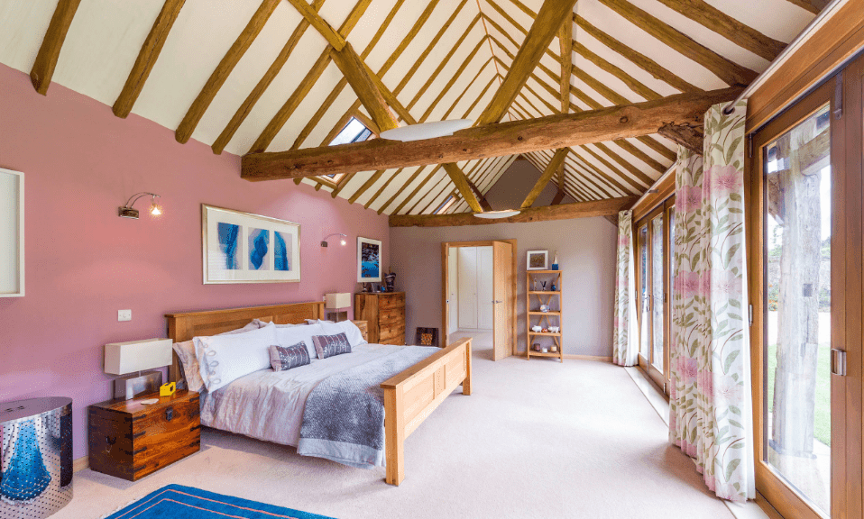 This master bedroom showcases a cathedral ceiling with exposed wood beams. It has panoramic windows dressed in floral drapery.