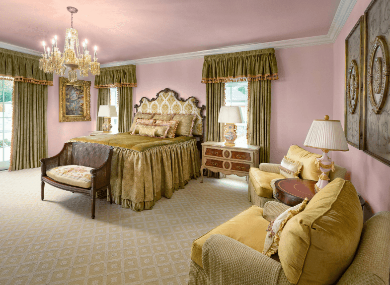 Pink master bedroom accented with earthy green curtains and bed along with armchairs over a diamond patterned rug.
