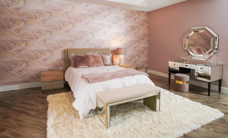 Gorgeous master bedroom showcases a white bed with a leather bench that lays on a patterned accent wall. It includes a mirrored vanity table paired with an octagon mirror and a dusty pink stool.