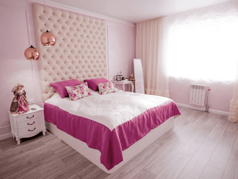 Charming bedroom boasts an oversized light pink tufted headboard fitted on the white bed. It is illuminated by a pair of copper pendants that hung over a white nightstand topped with a gorgeous doll.
