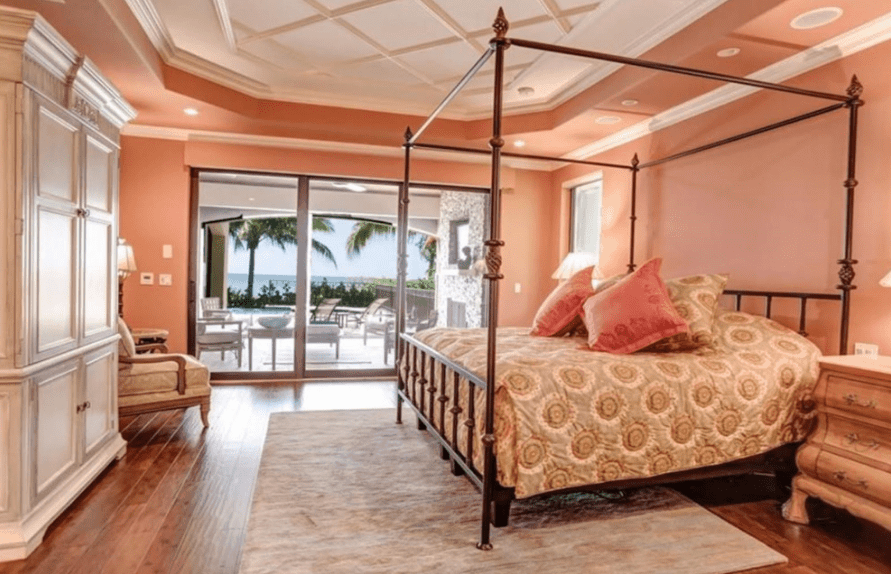 Traditional master bedroom showcases a coffered tray ceiling and glass door that opens to the patio. It has a canopy bed with printed bedding facing the wooden white wardrobe.
