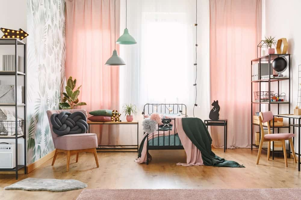 Pink bedroom with a small metal bed complementing the metal shelves racks and desks. It has a wooden pink upholstered accent chair fitted with a unique gray throw pillow.
