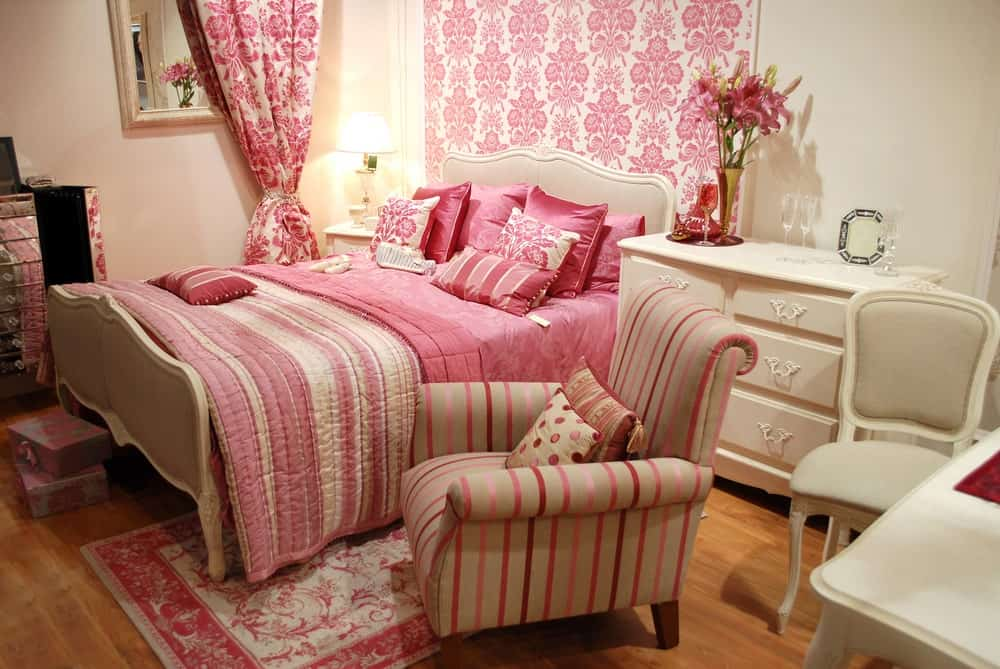 Charming master bedroom accented with a pink floral wallpaper that matches the curtain. It has an upholstered bed accompanied by a striped chair that sits on a pink rug over hardwood flooring.