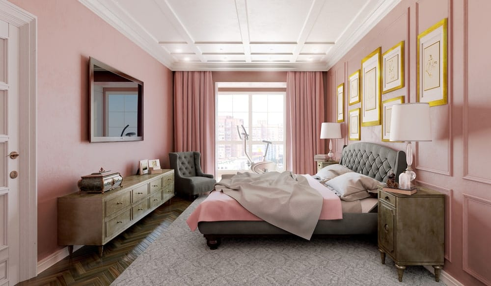 Sophisticated master bedroom boasts a white coffered ceiling and pink full wainscoted accent wall decorated with gold gallery frames.