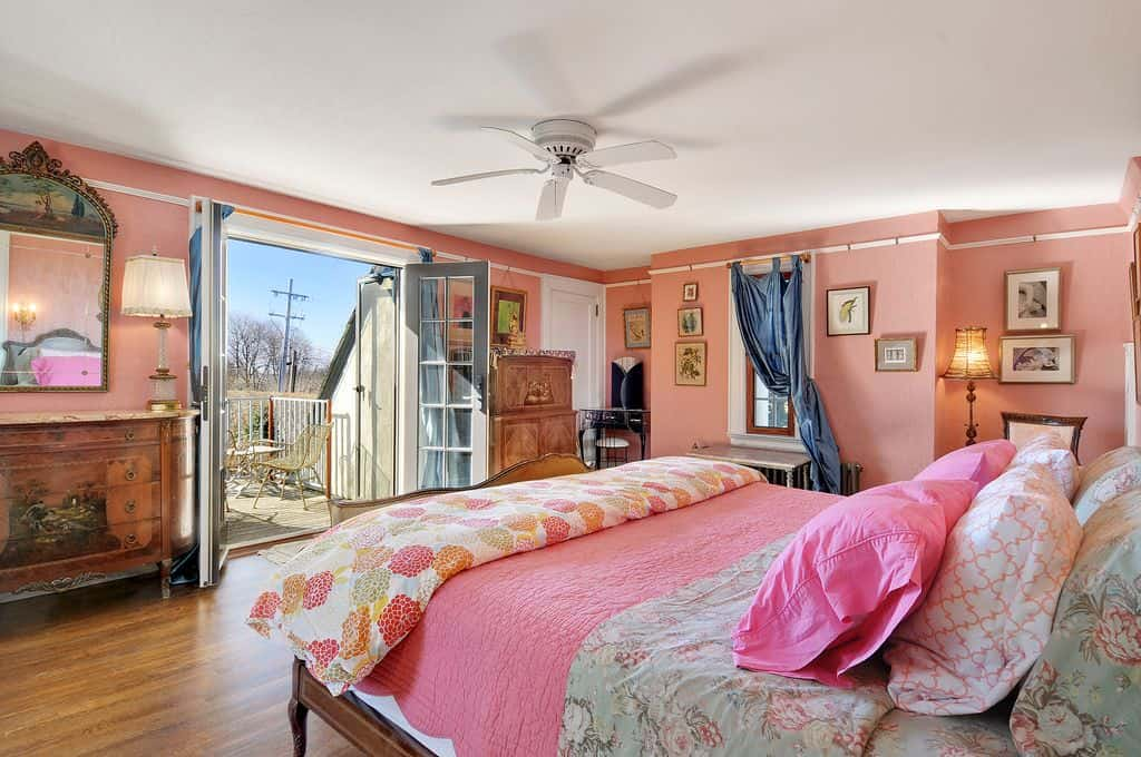 Pink master bedroom with a glass french door that opens to the balcony. It includes a wooden bed frame accompanied by a wooden chest drawer with an ornate mirror.