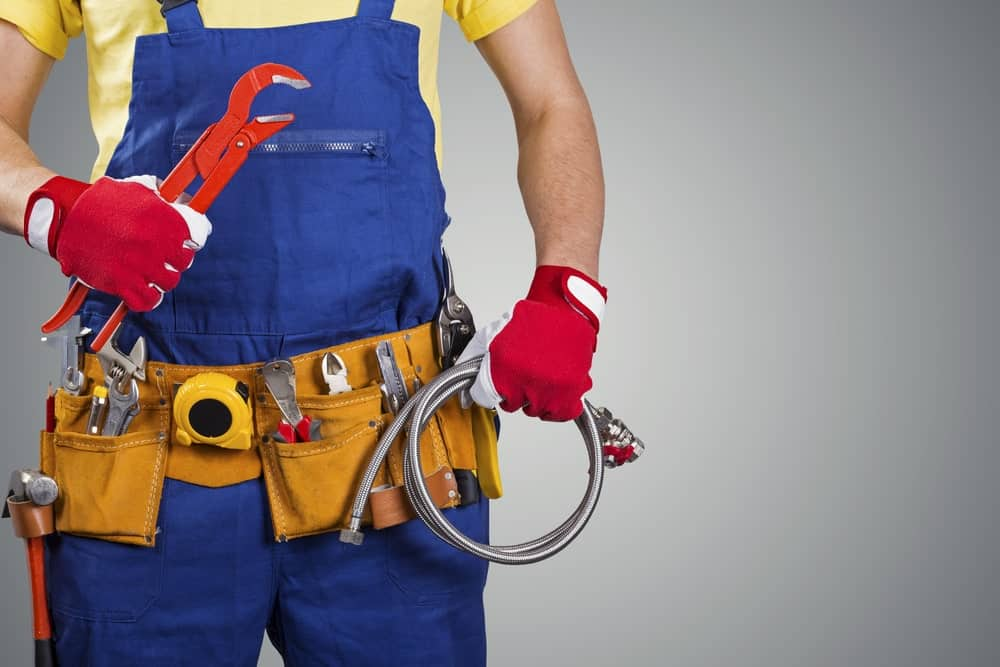 Plumber in uniform with tools.