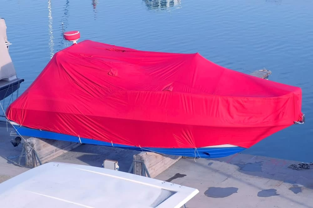 Docked boat covered in a pink polyester tarp.