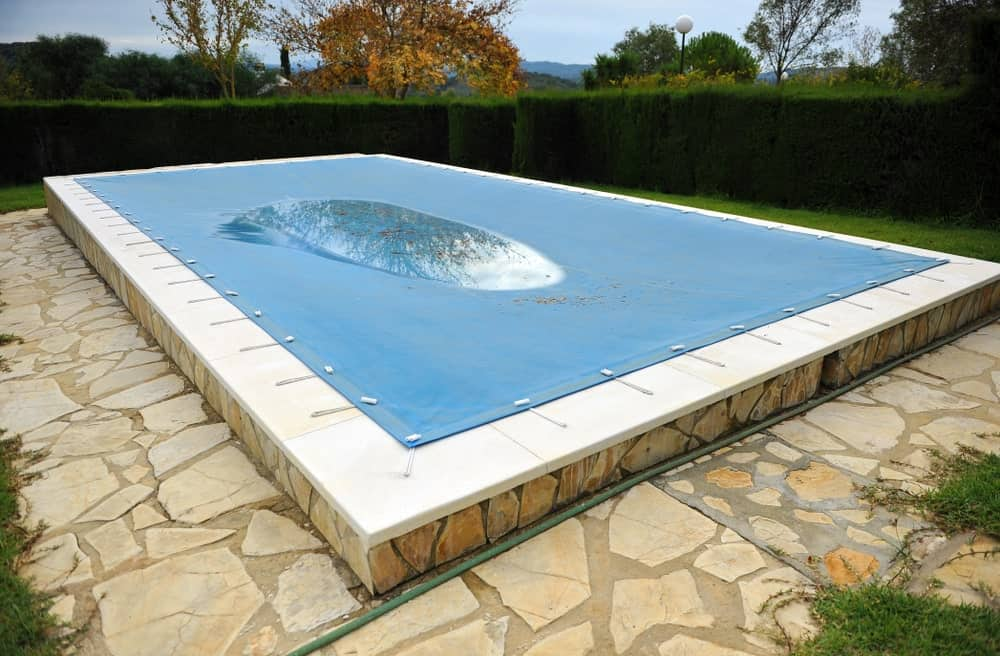Rectangular pool covered in a blue pool tarp.