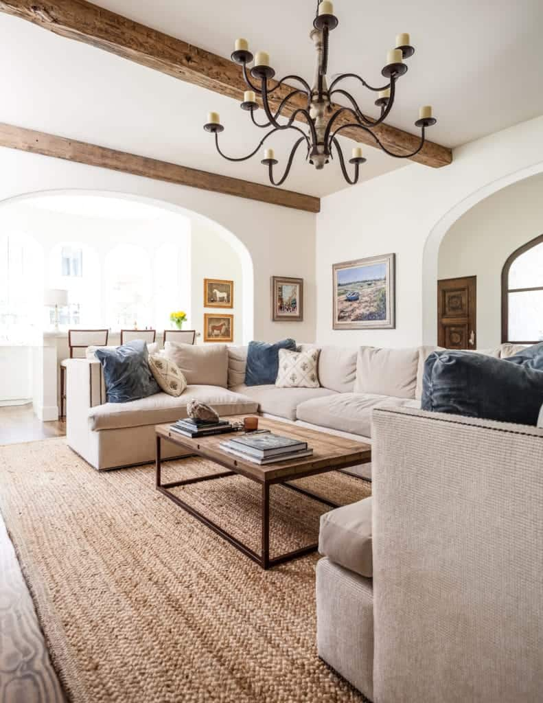 Gorgeous living room illuminated by an oversized traditional chandelier over a taupe U-shaped sectional. The exposed wood beams complement the coffee table that sits on a brown woven rug.
