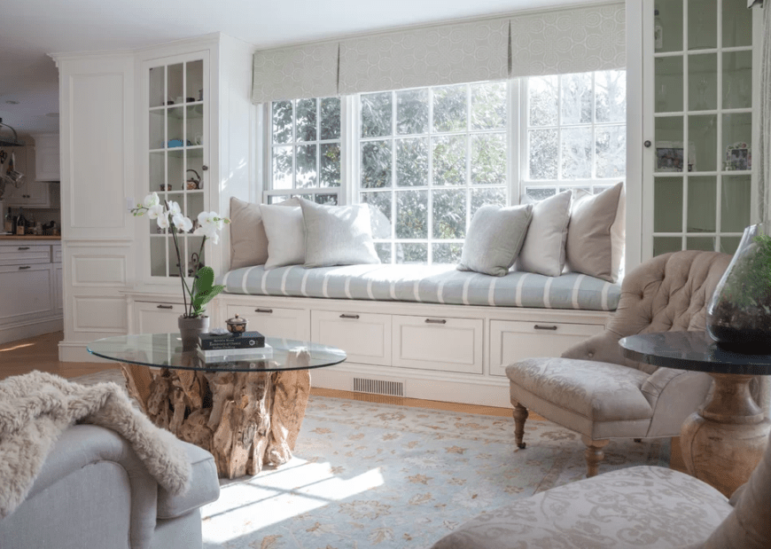 Bright reading nook features white framed windows covered in gray patterned roman shades and fitted with a blue striped cushion. It includes a beige tufted chair and tree stump coffee table.