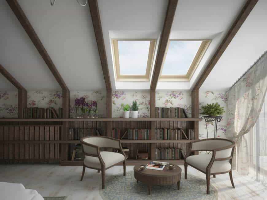 Rustic reading nook offers a shed ceiling framed with wood beams that extend to the built-in bookshelf. It has skylights suspended over two round back chairs and a wooden coffee table.