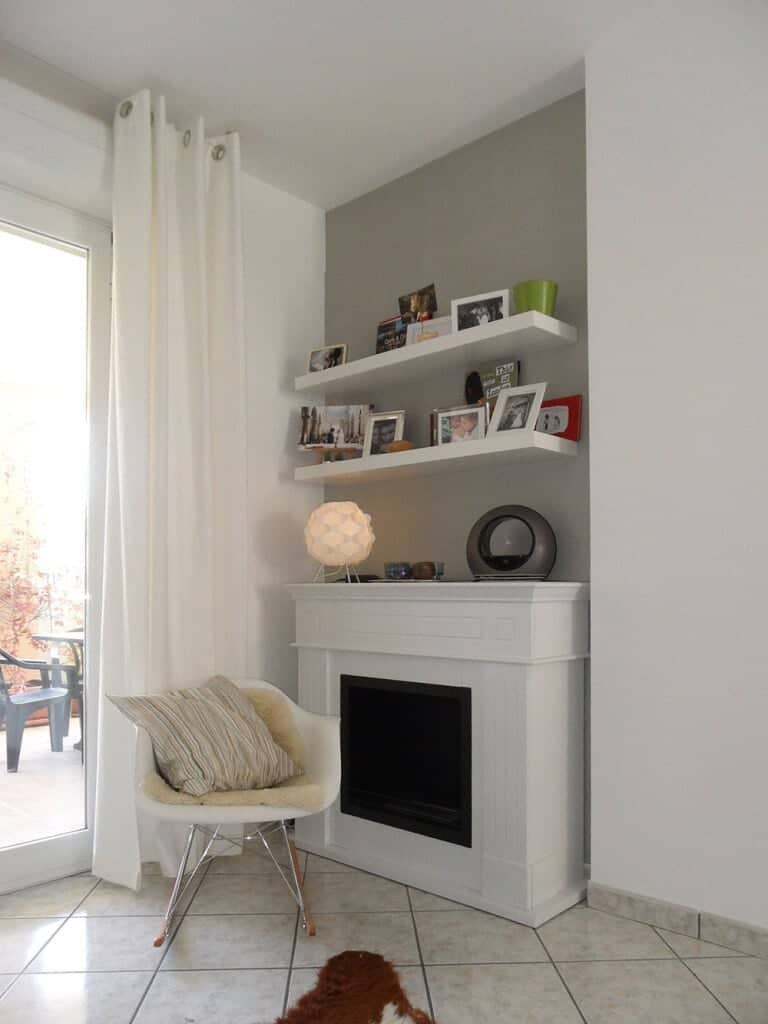 A fireplace is fixed to the gray inset wall below floating shelves in this reading nook. It is accompanied by a white chair filled with a striped pillow and a beige blanket.