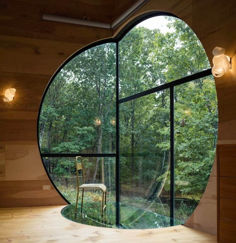 Cozy reading nook surrounded by natural wood walls and flooring. It is highlighted with a metal framed window in a spherical intersection cut.