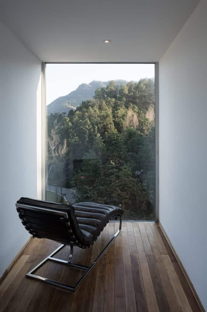 Minimalist reading nook offers a black chaise lounge that faces the floor to ceiling window overlooking a serene mountain view.