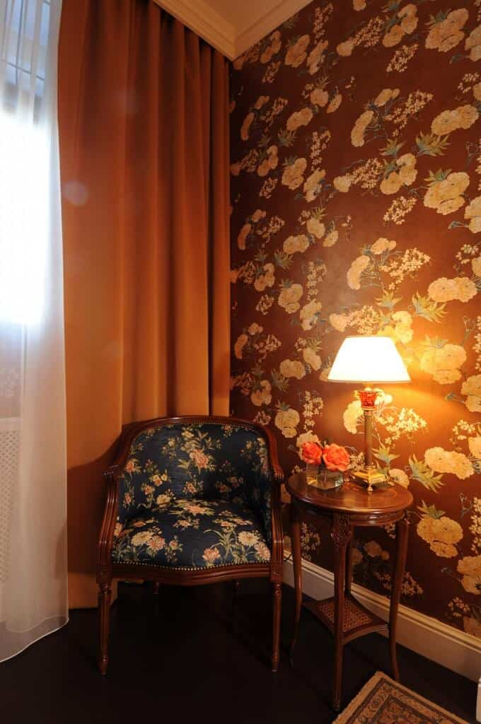 Warm reading nook clad in floral wallpaper that matches with the round back chair. It is paired with a round side table topped with a desk lamp.