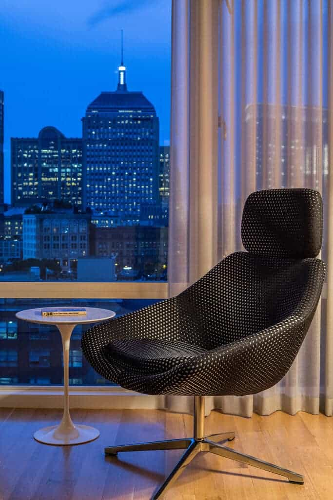 Reading nook with an amazing city view from the panoramic window. It includes a classy black dotted chair and sleek round table.