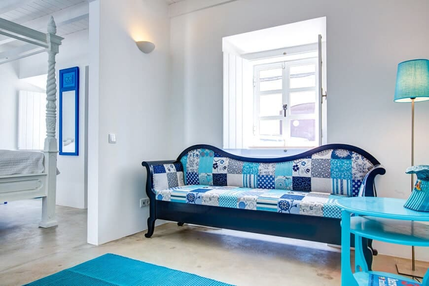 White reading nook accented with a blue checkered sofa and coffee table along with floor lamp and area rug over concrete flooring.