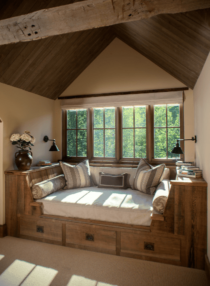 Cozy reading nook features a wooden daybed with built-in storage topped with white cushion and pillows and complements with the wood cathedral ceiling.