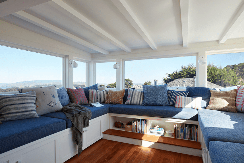 Beach style reading nook with U-shaped bench topped with blue sectional cushions and various styled pillows. It has panoramic windows overlooking a magnificent mountain view.