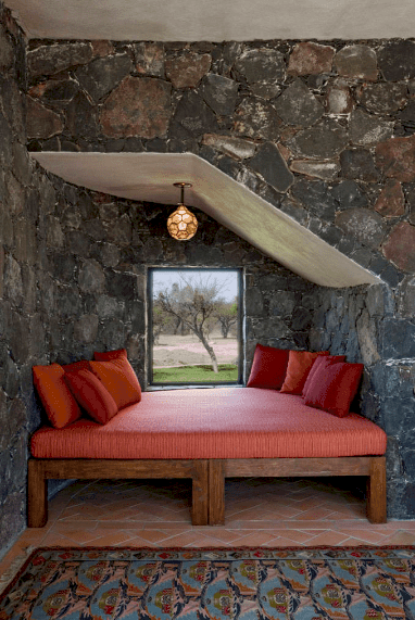 A reading nook placed in the corner of stone walls for optimum privacy. It has a wooden daybed fitted with red cushion and pillows.