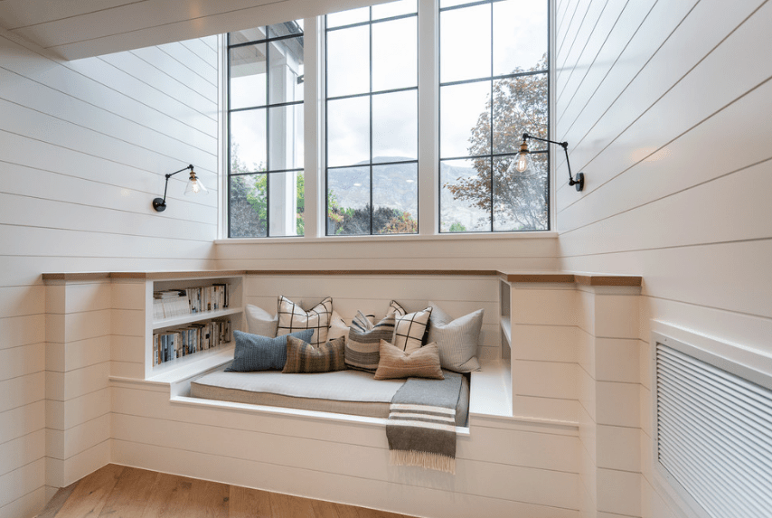 Bright reading nook showcases white shiplap walls and daybed filled with gray cushion and pillows. It is illuminated by wrought iron sconces and natural light from the framed window.