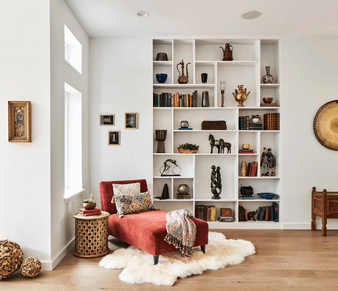 Fabulous reading nook boasts white walls mounted with wall arts and open shelving. It has a red chaise lounge that sits on a white shaggy rug over hardwood flooring.