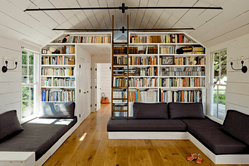 A wooden ladder lays on the built-in bookshelves in this spacious reading nook. It has a cathedral shiplap ceiling lined with black metal rods.