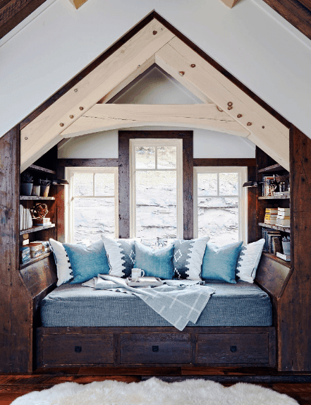 A wooden alcove reading nook accented with blue daybed and pillows. It is fitted with three drawers and open shelves on both sides.