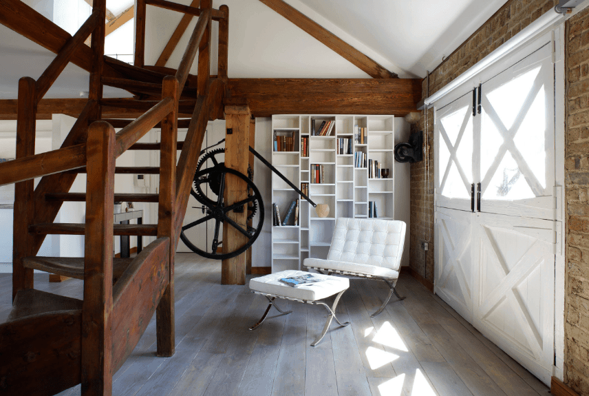 A double dutch door opens to a craftsman reading nook behind a wooden staircase. It is furnished with a white tufted sofa and matching ottoman along with built-in bookshelf.