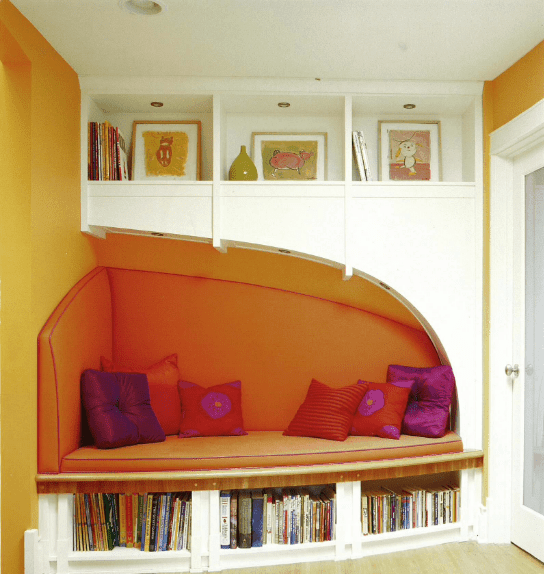 Colorful pillows lay on a built-in bench fixed to the mustard wall in this gorgeous reading nook. It has open shelves filled with wall arts and books.