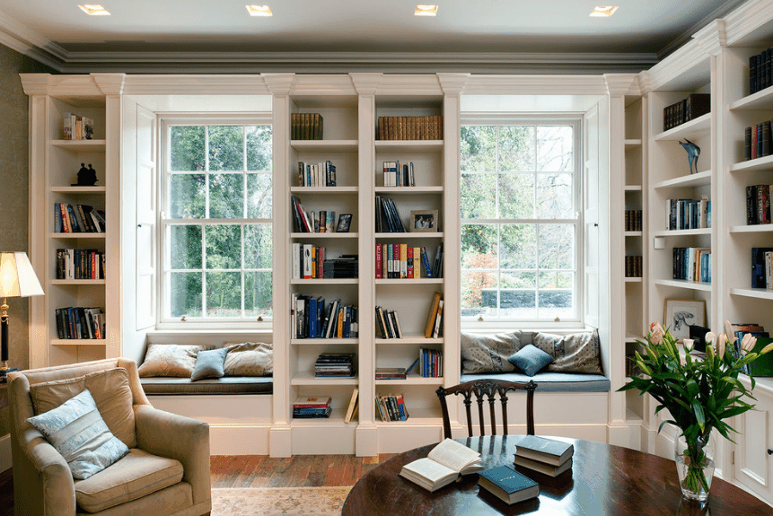Traditional family room with a reading nook by the window. It includes built-in benches fitted with brown and blue cushions that are topped with pillows.