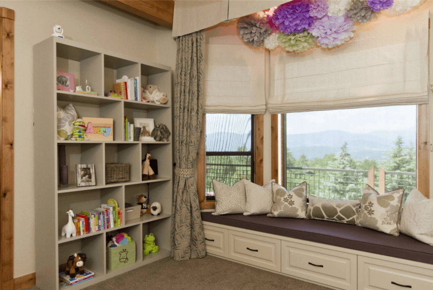 A taupe kid's room with reading nook styled with lovely floral decors fixed above the roman shades. It includes a bookcase filled with toys and books.