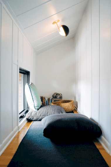 A lengthy reading nook offers white wainscoted walls and hardwood flooring topped with a deep blue runner. It is illuminated by a brass globe lamp mounted on the shed ceiling.