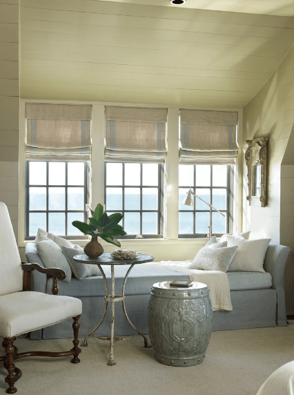 Beach style reading nook features triple windows covered with beige roman shades. It has a white chair and blue bench paired with metal and drum tables.
