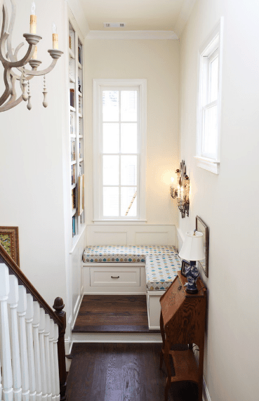 A corner reading nook situated next to the staircase landing. It has an L-shaped bench topped with charming cushions and fixed to the white wainscoting.