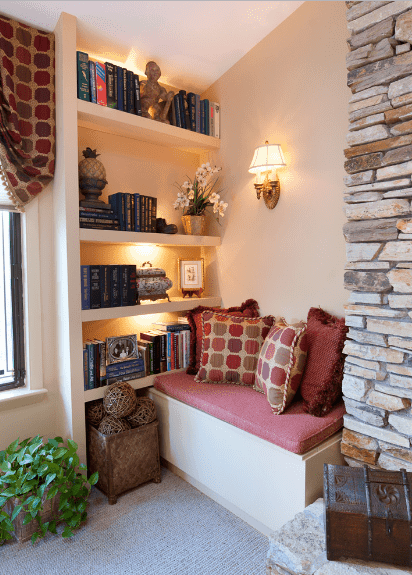 Red pillows and cushion lay on the built-in bench in this reading nook. It includes a bookshelf lighted with a sconce that's mounted on the peach wall.