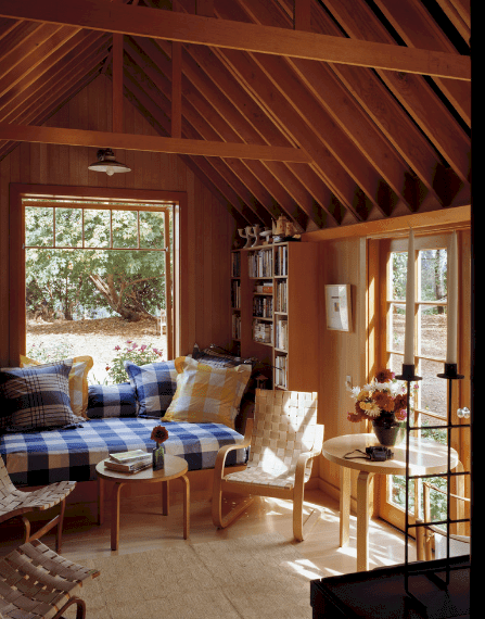 An all wood reading nook showcases woven chairs and round tables along with checkered blue cushions and yellow pillows.